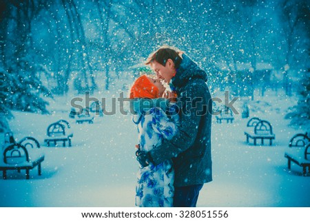 beautiful young couple kiss on snow park background - stock photo