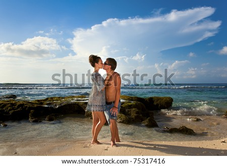 Beautiful young couple kissing on the coast - stock photo