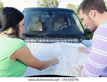 Beautiful young couple looking at the map pointing the places on it standing in front of the car - stock photo