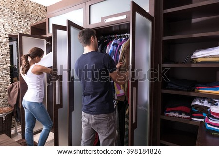 Beautiful young couple looking dresses in the dressing room. - stock photo