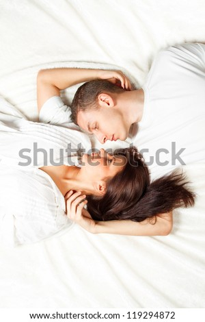 Beautiful young couple lying down with their heads together - stock photo