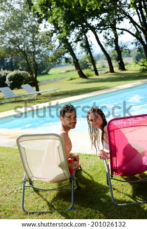 beautiful young couple man woman during summer holiday in swimming pool resort - stock photo