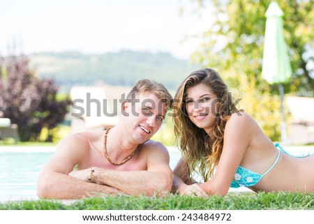 Beautiful Young Couple Next to Swimming Pool - stock photo