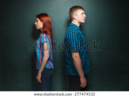 Beautiful Young Couple Over Dark Green Wall. They stand a back to each other. Quarrel, conflict. Hard time in relationships. Love story. Red-haired woman and blonde man in check shirts.  - stock photo