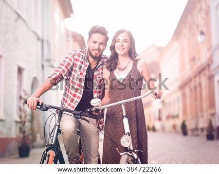 beautiful young couple posing beside bicycle on a street in a medieval town, sunny day - stock photo