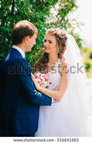 beautiful  young couple posing in the park on a background of trees - stock photo