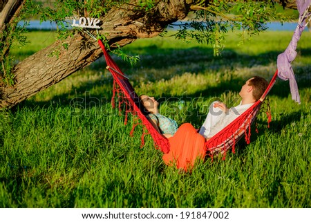 beautiful young couple relaxing in a hammock on the nature