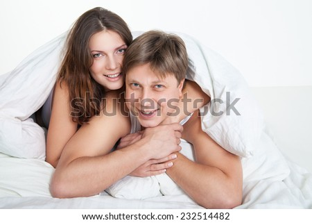Beautiful young couple relaxing in bed at home over white