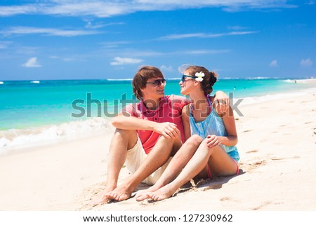 beautiful young couple sitting and having fun on beach - stock photo