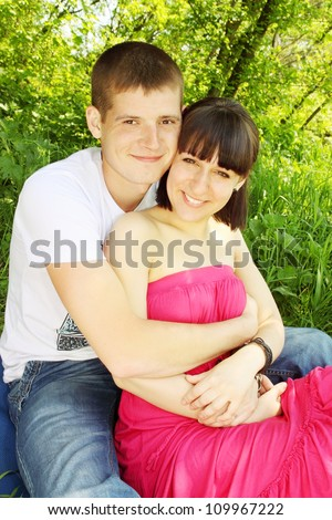 Beautiful young couple sitting arm in arm