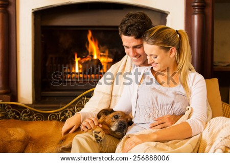 beautiful young couple sitting by fireplace with their pet dog at home - stock photo