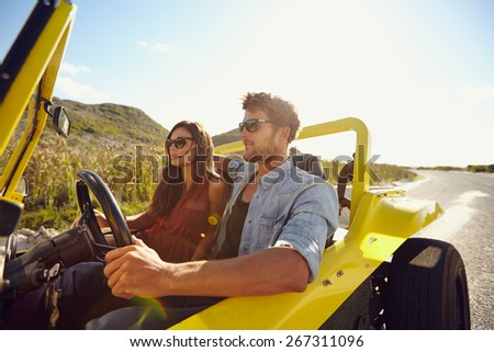 Beautiful young couple sitting in their car and enjoying the road trip. Man driving a car on an open road. Couple on summer holiday. - stock photo