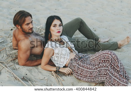 beautiful young couple sitting on the sand on the beach in woode