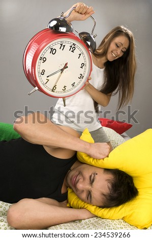 Beautiful Young couple sleeping in bed in the morning. Sleepy boyfriend waking up with alarm clock. - stock photo