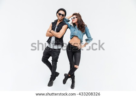 Beautiful young couple standing and posing over white background - stock photo