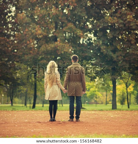 beautiful young couple tenderly holding hands - stock photo