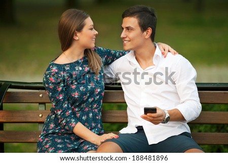 Beautiful  young couple using a smartphone outdoors.