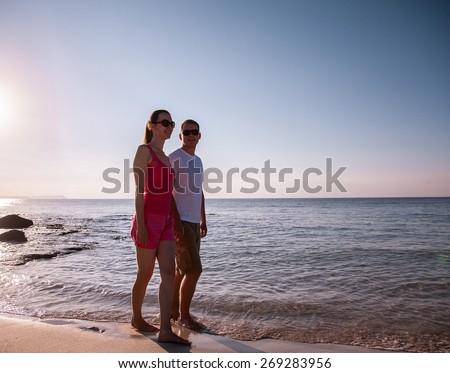 Beautiful young couple walking along the seashore - stock photo