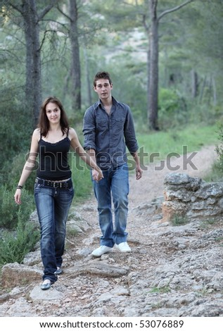 Beautiful young couple walking on a forest path