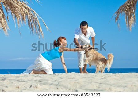 Beautiful young couple with a dog at sea - stock photo
