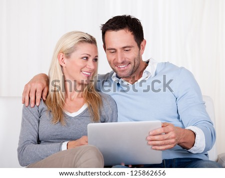 Beautiful young couple with lovely smiles sitting side by side on a sofa looking at a tablet together - stock photo