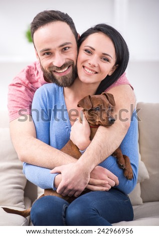 Beautiful young couple with their dog - zwergpinscher on their living room couch. - stock photo