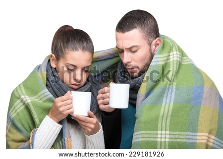 Beautiful young couple wrapped a warm blanket, are drinking hot tea. - stock photo