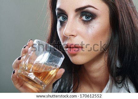 beautiful young crying woman in depression, crying and drinks alcohol Face close up - stock photo