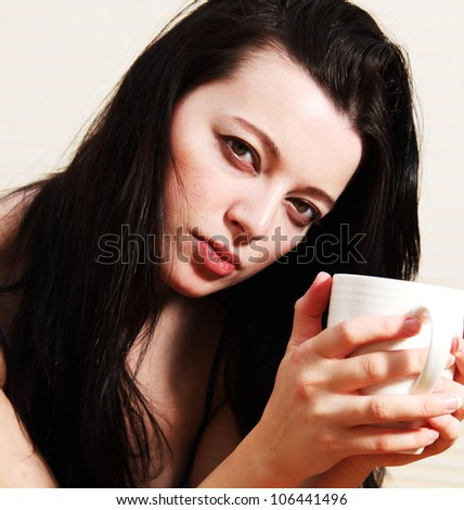 Beautiful young, dark haired woman holding white cup - stock photo