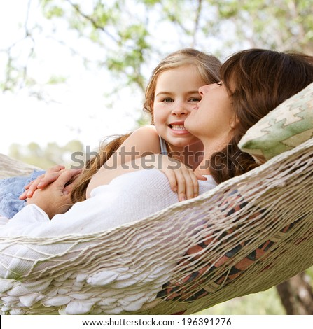 Beautiful young daughter girl and her mother hugging and enjoying laying together in a hammock during a summer holiday in a home vacation garden during a sunny day. Outdoors relaxing lifestyle. - stock photo
