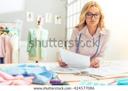 Beautiful young designer in eyeglasses is holding a piece of paper and examining some sketch while working in dressmaking studio - stock photo