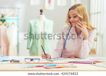 Beautiful young designer is drawing sketches, talking on the mobile phone and smiling while working in dressmaking studio - stock photo