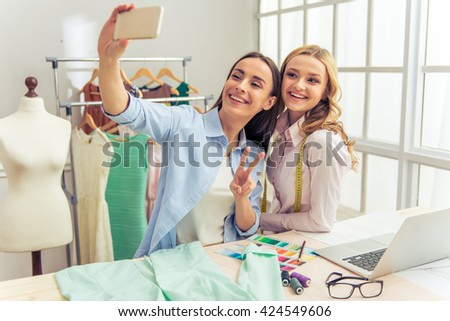 Beautiful young designers are making selfie using a smart phone and smiling while working in dressmaking studio - stock photo