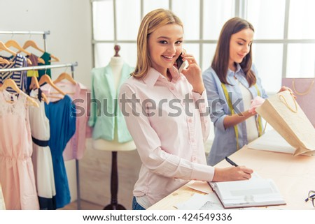 Beautiful young designers are working in dressmaking studio. One girl is talking on the mobile phone, looking at camera and smiling - stock photo