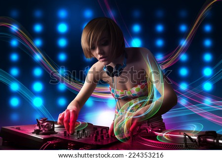 Beautiful young Dj girl mixing records with colorful lights