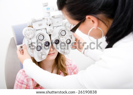 Beautiful young doctor inspect a patient in ophthalmology labor - stock photo