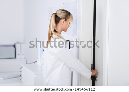 Beautiful young doctor opening the door in the lab