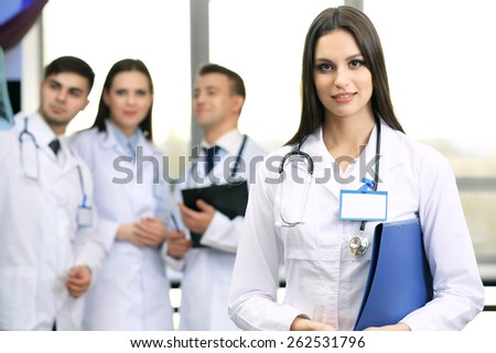 Beautiful young doctor with team in conference room - stock photo