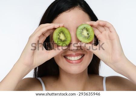 beautiful young ethnic brunette showing slices of kiwi fruit  - stock photo