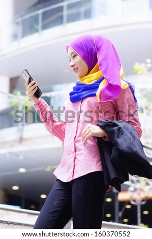 Beautiful young executive using tablet phone outdoor excited expression