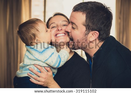 Beautiful young family. Father and son kissing the mother - stock photo