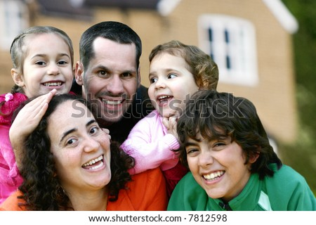 Beautiful young family having fun playing with house in the background. - stock photo