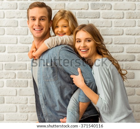 Beautiful young family hugging, looking in camera and smiling while standing against white brick wall - stock photo