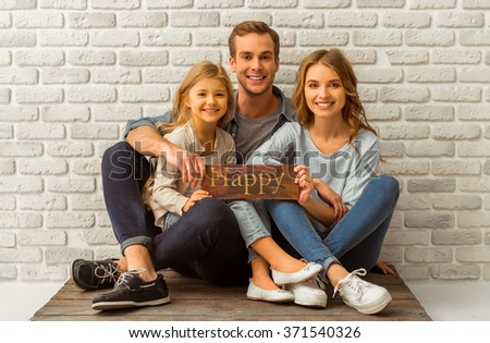 Beautiful young family hugging, looking in camera, smiling and holding a wooden plate while sitting against white brick wall - stock photo