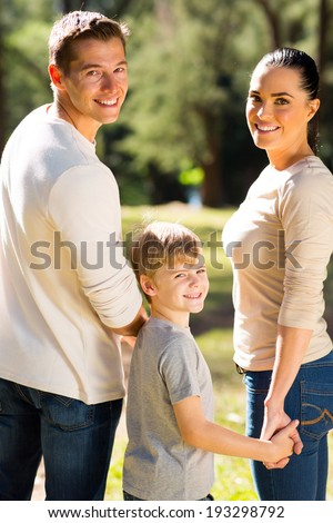 beautiful young family looking back in forest
