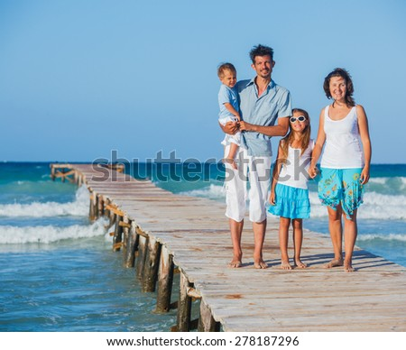 Beautiful young family of four walking along wooden jetty - stock photo
