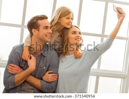 Beautiful young family smiling and making selfie while sitting near the window at home - stock photo