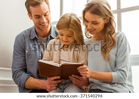 Beautiful young family smiling and reading a book while sitting near the window at home - stock photo