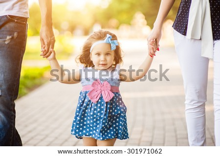 Beautiful young family together go through the alley - stock photo