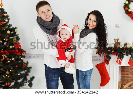 Beautiful young family, with little baby in red costume, posing in decorated room with christmas tree on the background, waist up - stock photo